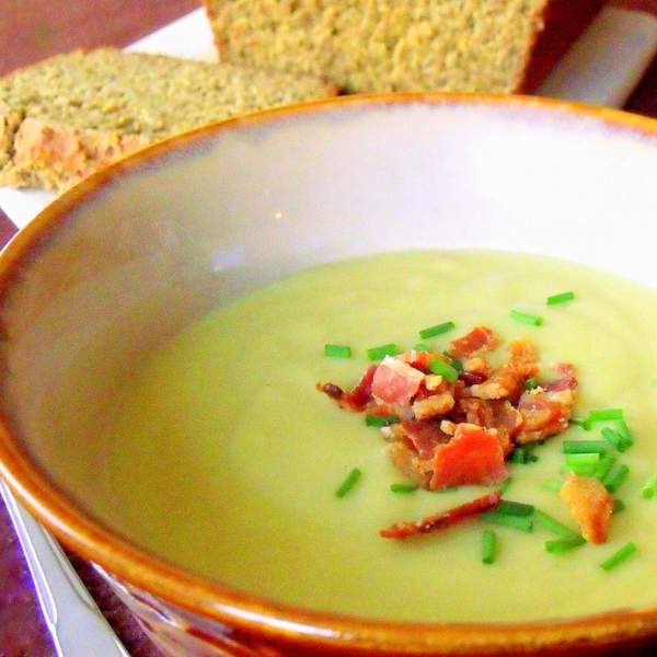 Traditional Irish potato and leek soup in a brown rimmed bowl served with sliced Irish brown bread.