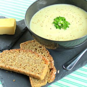 Traditional Irish potato soup in a black bowl with brown wholewheat bread and butter