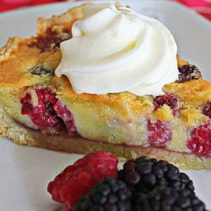 Raspberry and blackberry almond tart on a plate with a swirl of cream and fruit