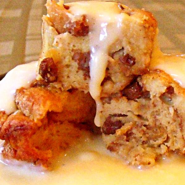 Cinnamon raisin bread pudding with custard dripping down over it.