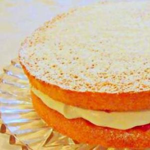 Irish cream and jam sponge cake with sugar dusted on top