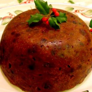 Irish Christmas or plum pudding on a plate with a holly decoration