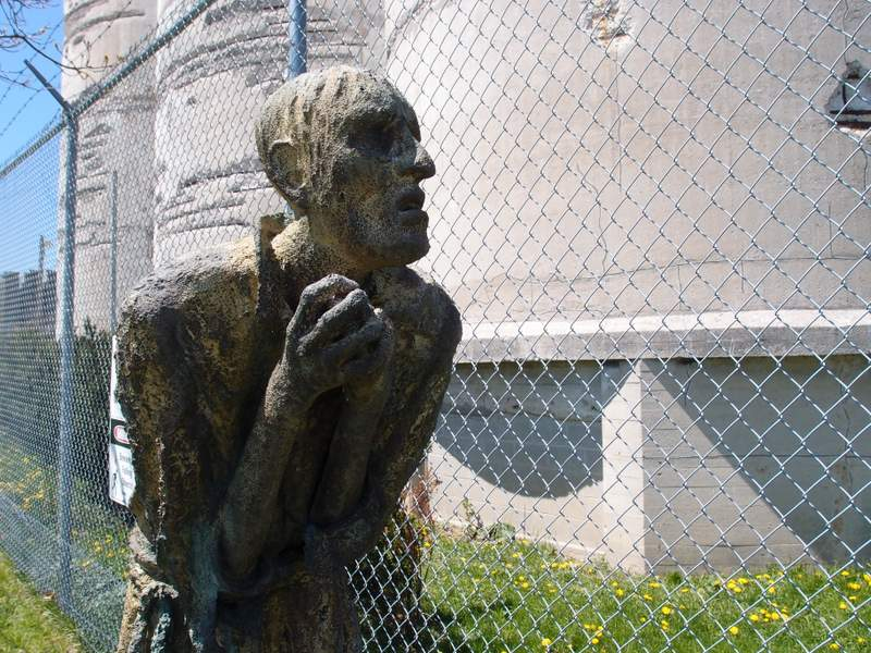 A statue of a man clasping his hands that is standing in front of a fence