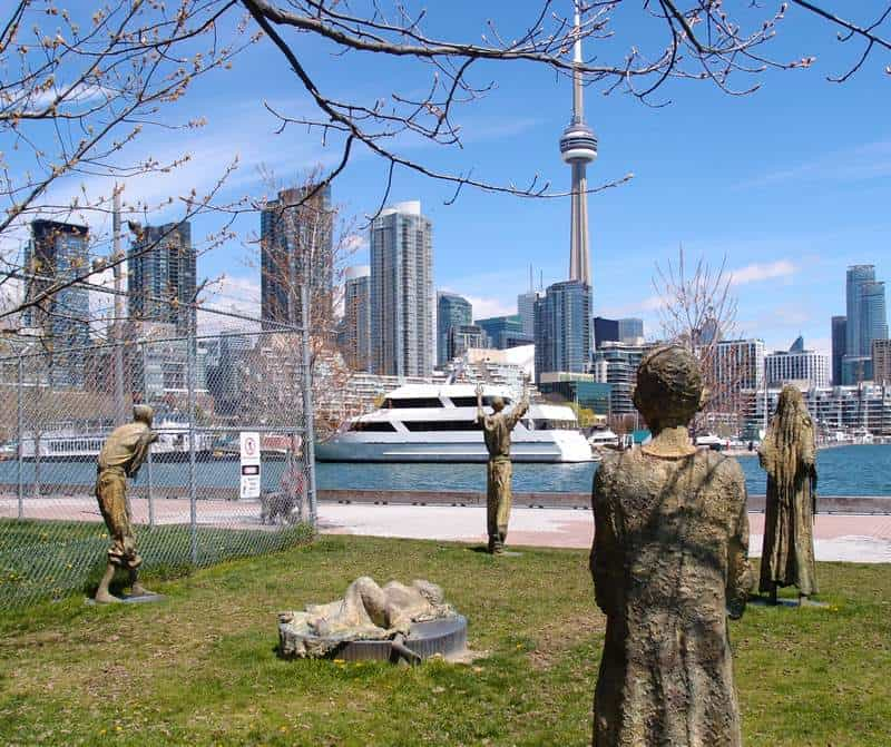 A group of statues that are standing in the grass opposite a city skyline