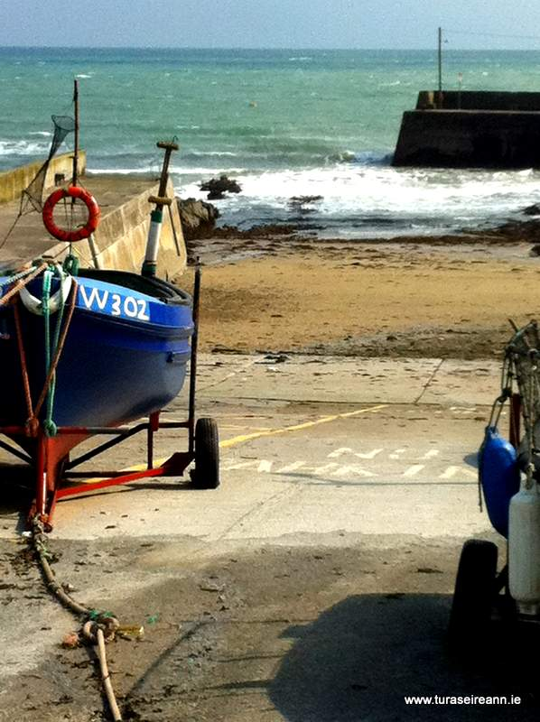An Irish pier with a blue boat on a trailer