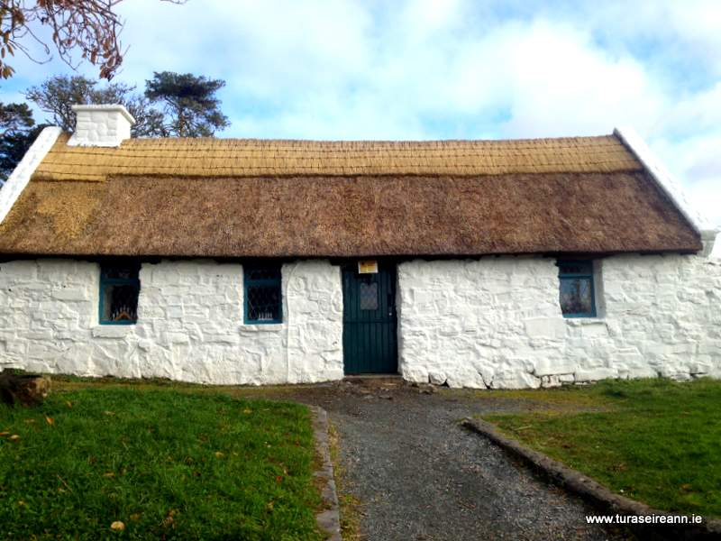 A thatched cottage with white washed walls and a black door