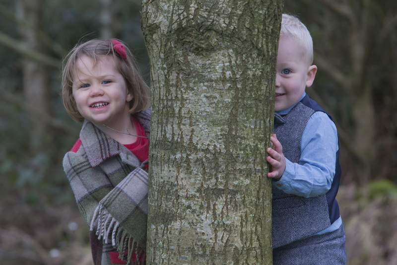 Young boy and girl wearing tweed outfits peeping around a tree