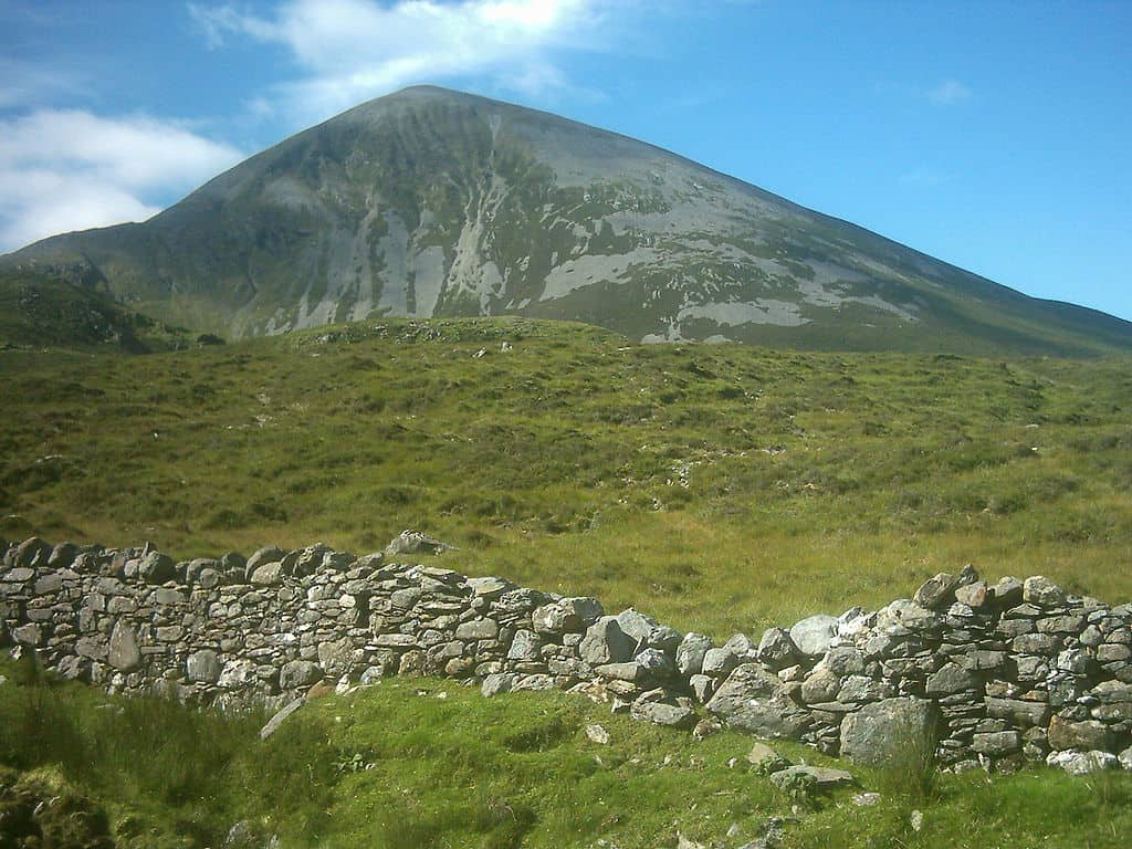 A mountain with steep shale slopes with a stone wall in the foreground