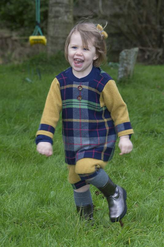 Young girl runnng wearing a blue and yellow plaid tweed pinafore or jumper