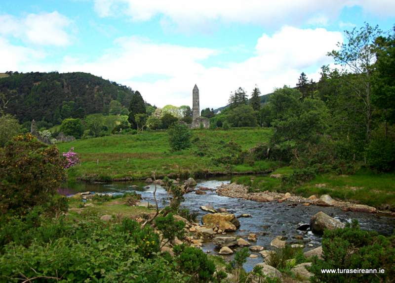 A round tower in a green field beside a river with stones