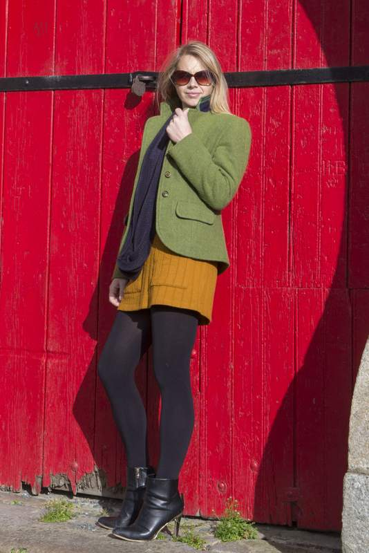 Green tweed ladies jacket and a mustard tweed skirt worn by a woman leaning against a red barn door