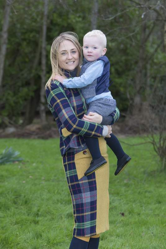 Lady wearing a blue plaid tweed suit with her little boy wearing a tweed vest and knickerbockers