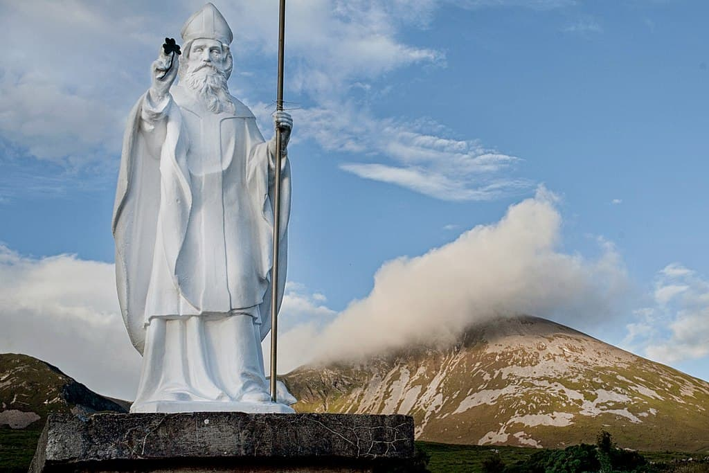 Statue of Saint Patrick beside a mountain with a cloud over the peak