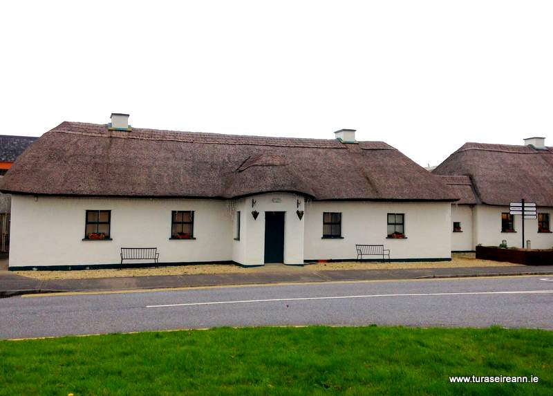 A long white cottage with a straw thatched roof