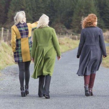 Three women wearing tweed coats walking down a road