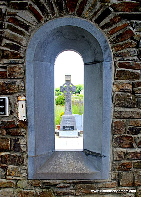 Celtic cross viewed through an arched opening on a stone wall