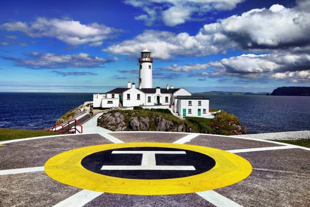 The helicopter pad in front of a lighthouse beside the ocean