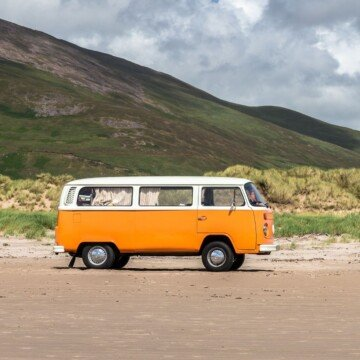 Orange and white vintage minivan beside a mountain slope