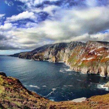 Steep ocean cliffs beneath a puffy cloudy sky