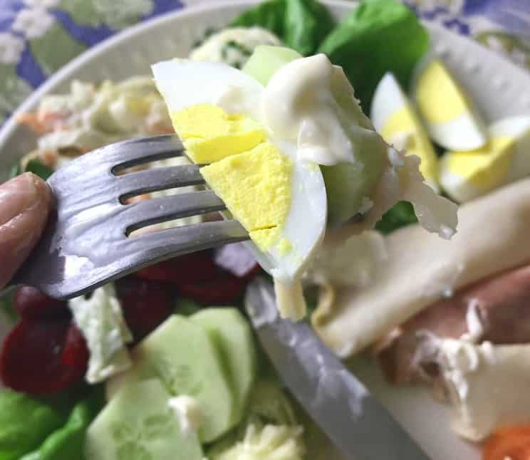 Eating an Irish salad by placing ingredients on the back of a fork.