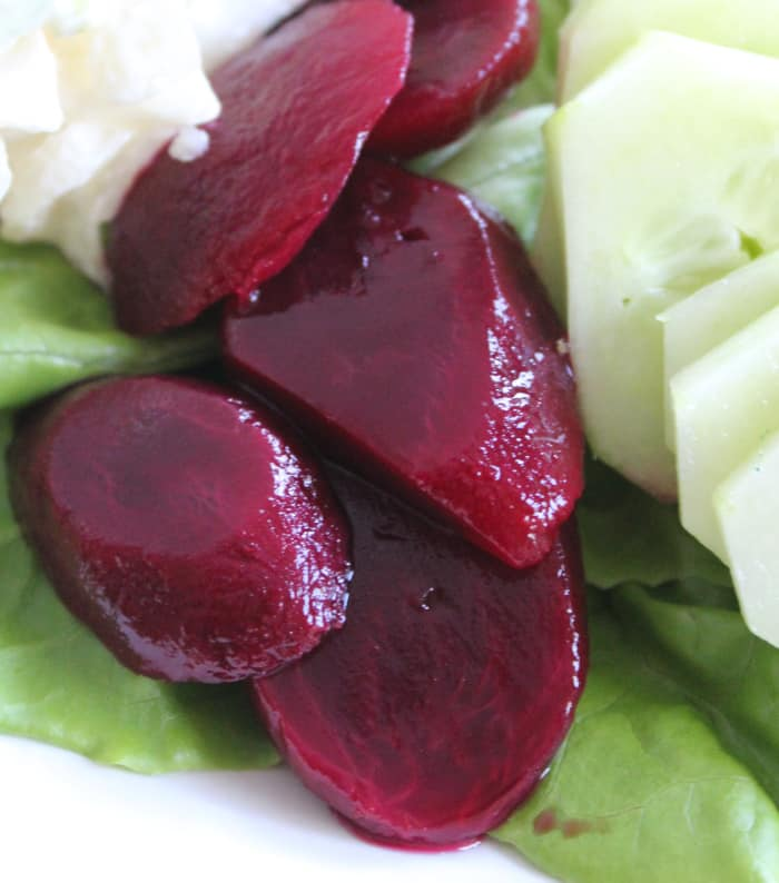 Sliced pickled beets are placed beside cucumber on an Irish salad plate.