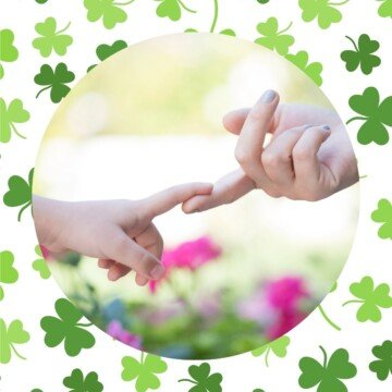 Mother and child touching fingers with a shamrock background