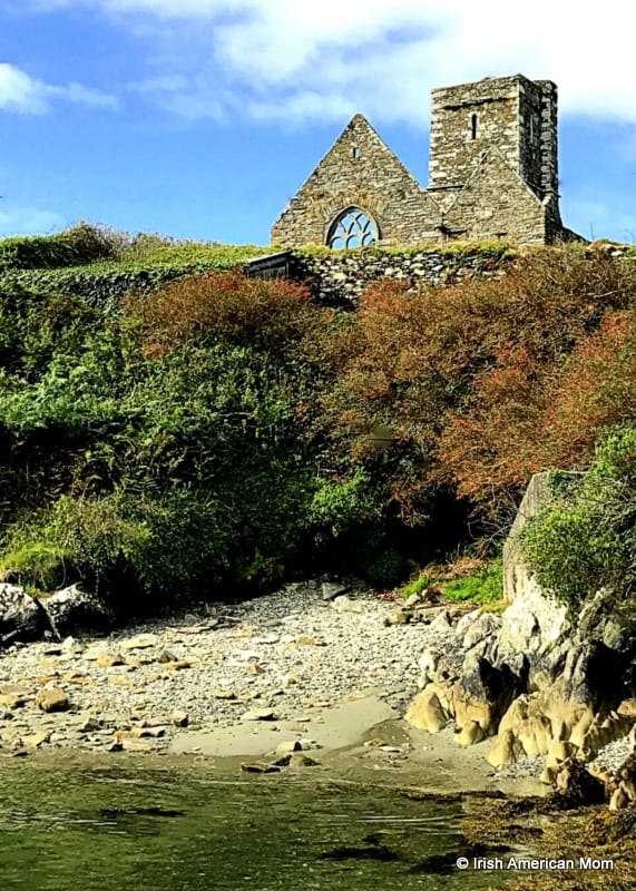 An old church wall on top of a cliff above a sandy beach