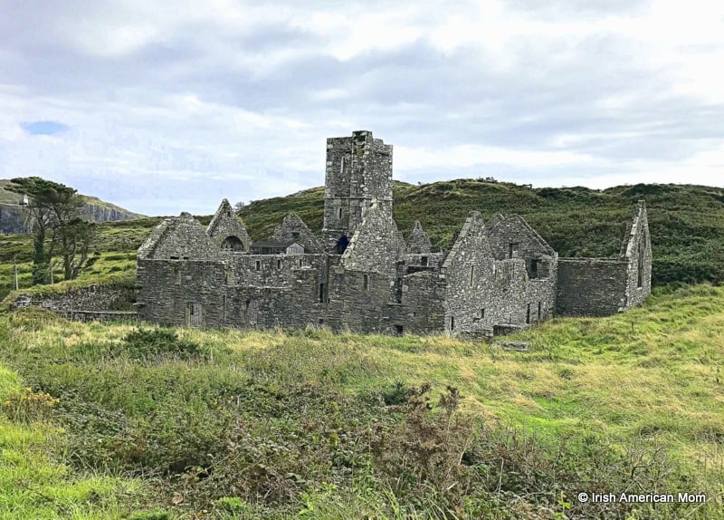 A ruined stone building on top of a grass covered field