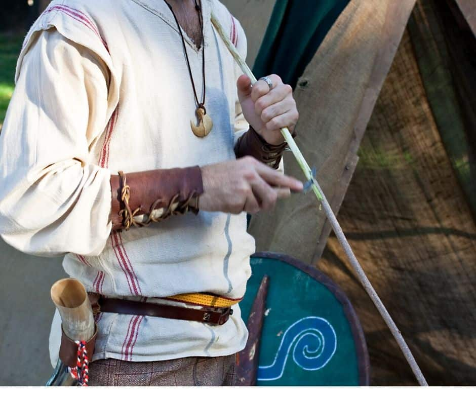 A Celtic warrior fashions a wooden bow with a knife