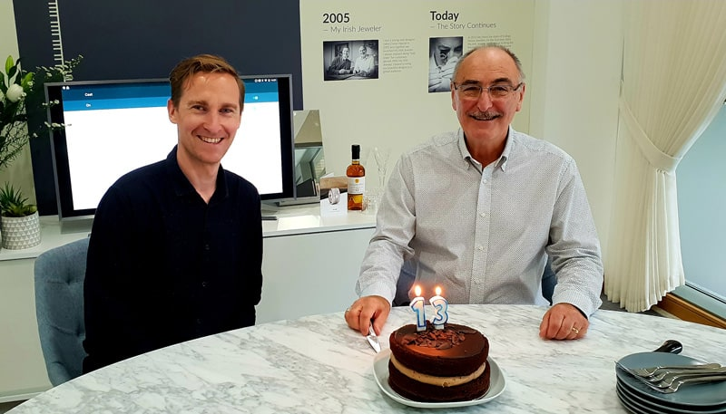 Two men sitting at a table with a cake