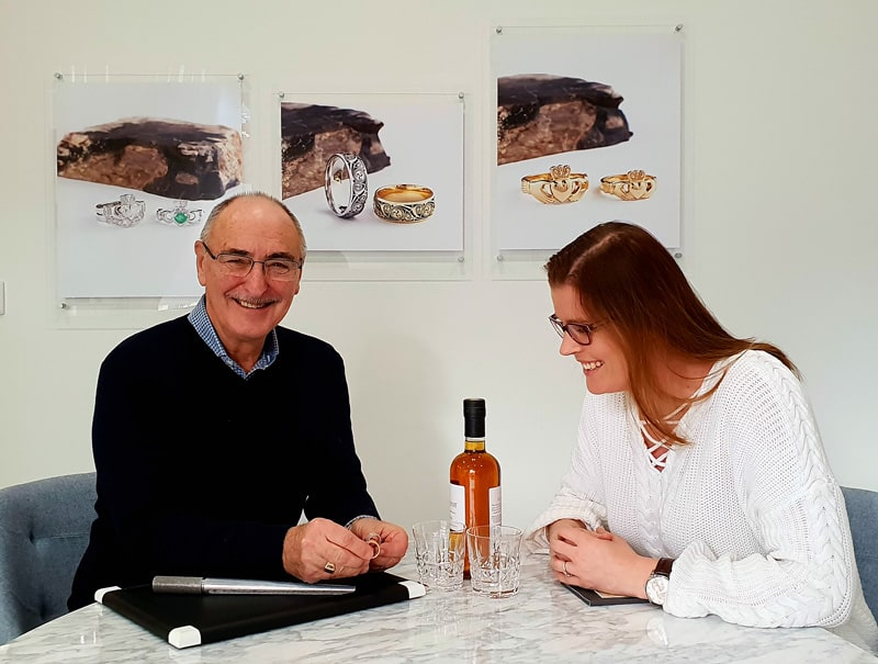 A man and woman sitting next to a bottle of wine