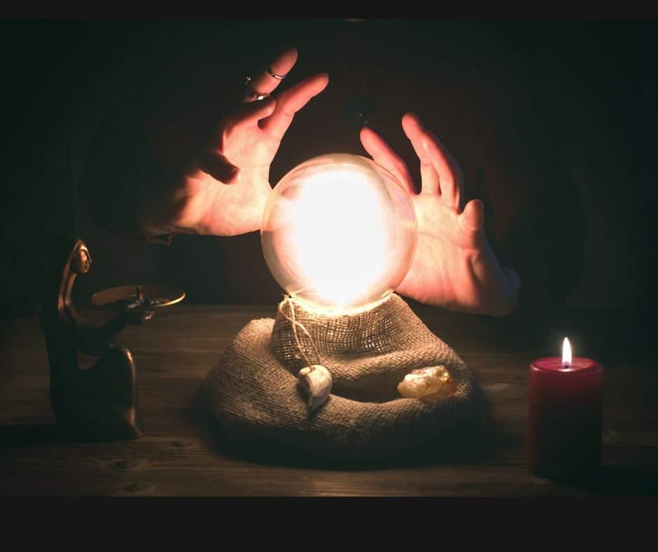 Hands circling a crystal ball that is illuminated