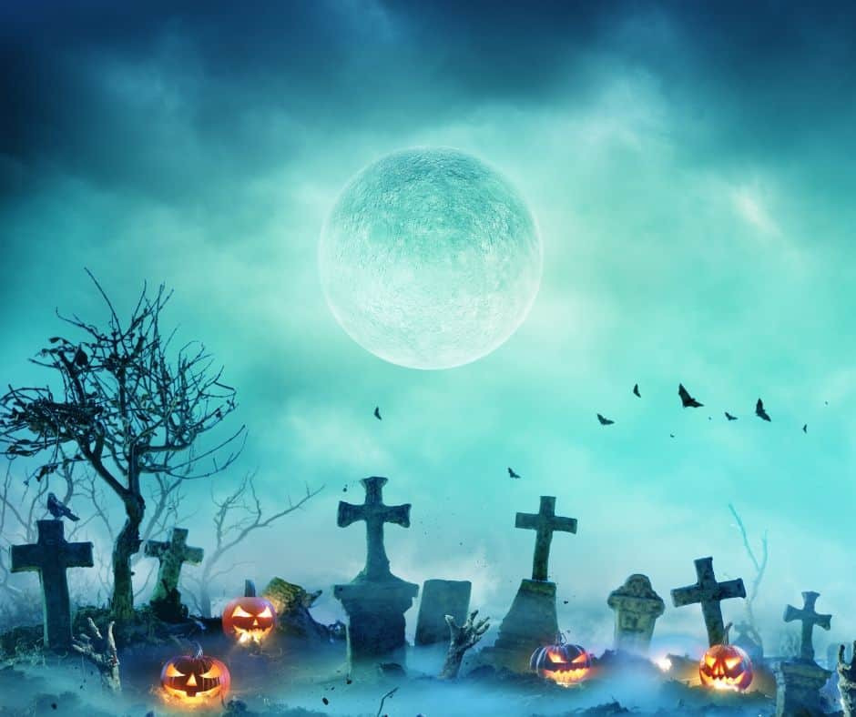 A full moon in a cloudy illuminated night sky over gravestones and bright jack o'lanterns