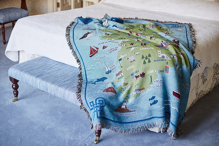 A blue and green cotton throw featuring a map of Ireland draped over the end of a bed.