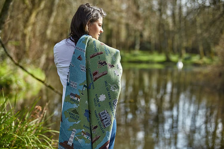 A woman drapes a cotton throw over her shoulder, featuring a map of Ireland
