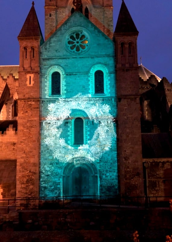 A white wreath illuminated on the side of Christchurch Cathedral in Dublin