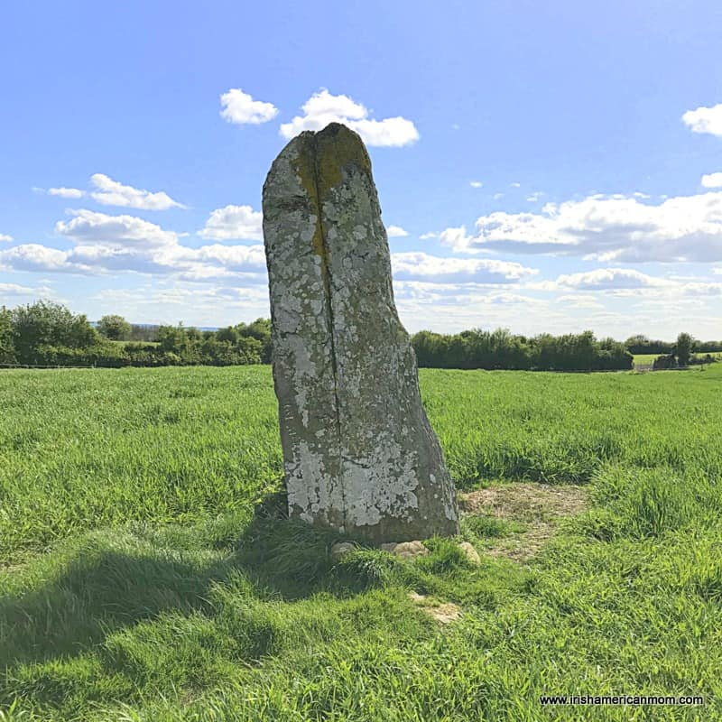 A large standing stone in the center of a green grassy field