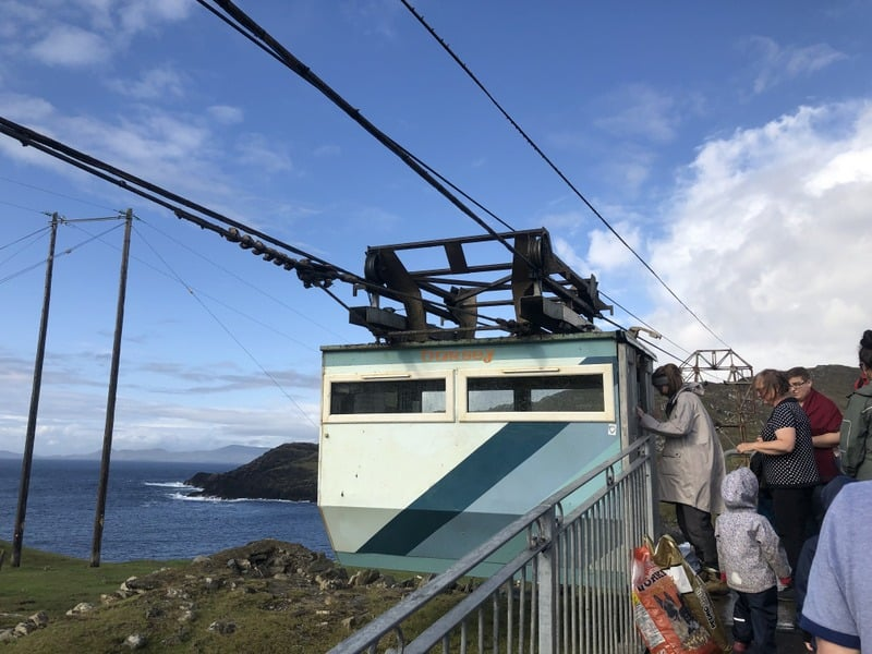A family board a cable car by the ocean in Ireland
