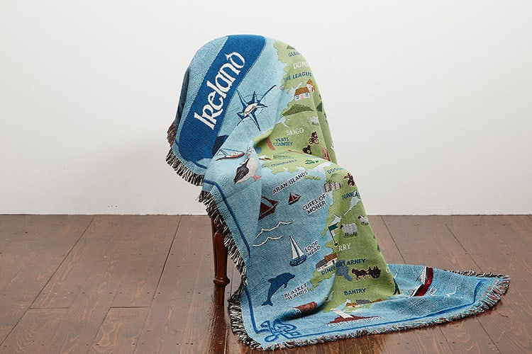 A green and blue Map of Ireland cotton throw displayed on a chair