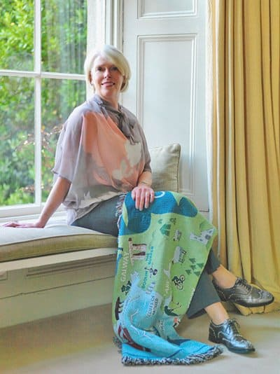 Sitting on a window seat with a Map of Ireland throw across the knees