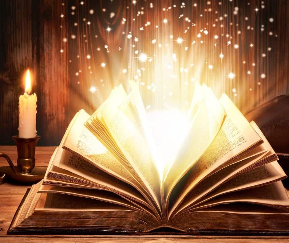 A candle beside a book of fairy tales as sparkles escape from the pages