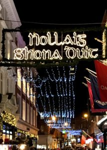A Happy Christmas sign in Irish illuminated over the streets of Dublin