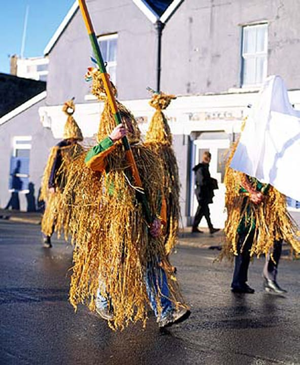 Straw boys in costume parading through the streets of an Irish town