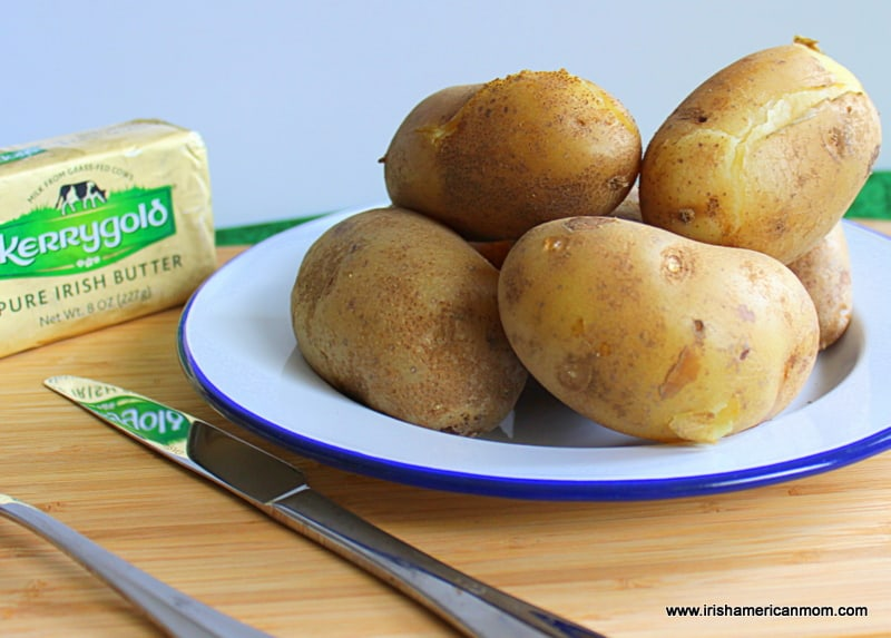 Boiled floury Irish potatoes with split skins on a plate