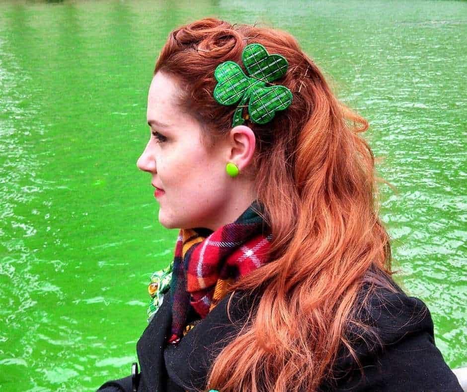 A red haired Irish lady wears a green shamrock hair accessory by a river dyed green