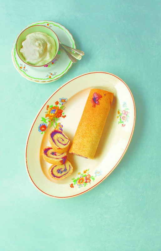 A jam swiss roll on a floral oval plate with three slices cut beside a bowl of whipped cream