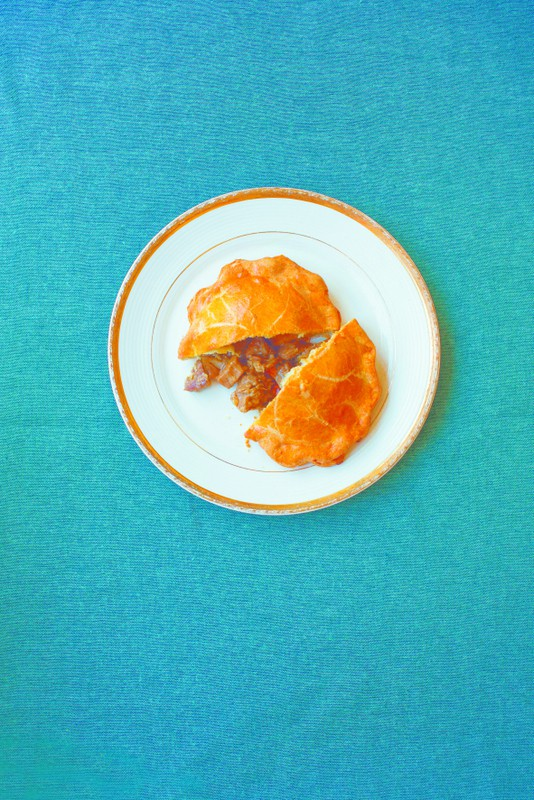 A venison pie cut in half on a white plate with a golden rim