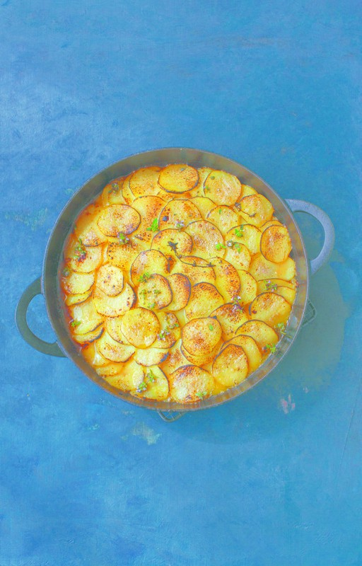 Aerial shot of a lamb hot pot with golden sliced potatoes on top