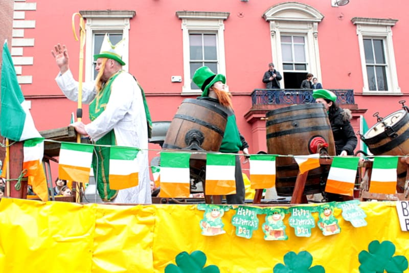 A parade float with Saint Patrick holding a crozier surrounded by beer barrels