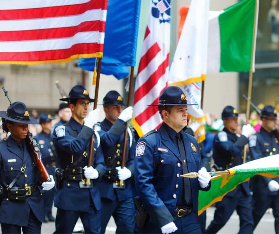A group of policemen march in a Saint Patrick\'s Day Parade holding flags from different nations and groups